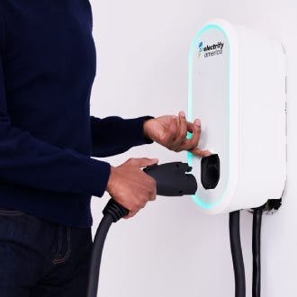 Level 2 electric vehicle home charger plug attaching to home charger plug holster.